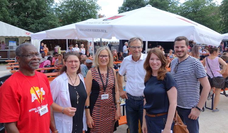 Olatunde Sadiq, Ute Vogt, Alice Vetter-Takin, Werner Wölfe, Anna Christmann und Raiko Grieb stehen auf dem Erwin-Schoettle-Platz, wegen der Hitze unter Sonnenschirmen