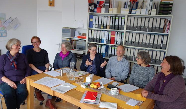 Zu acht sitzen die Geschäftsführerin, die MitarbeiterInnen der deab und Ute Vogt am Besprechungstisch vor einem Regal voller Leitzordner.