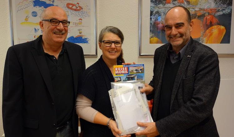 Herr Paul und Herr Petri übergeben Frau Vogt mehrere Klarsichthüllen mit den gesammelten Unterschriften