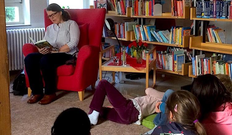 Vor einem Bücherregal sitz Ute Vogt im roten Lehnstuhl, um sie scharen sich die lauschenden Kinder