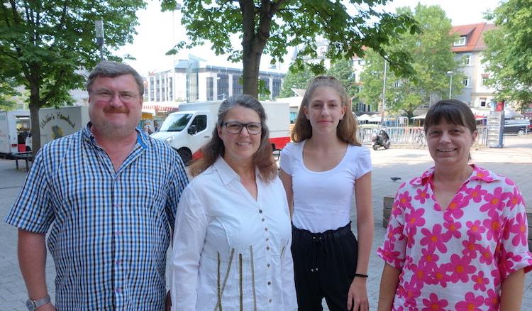 Lara Joyce, Ute Vogt und die beiden Mitarbeiter stehen auf dem Wilhelmsplatz, im Hintergrund ist Markttag.