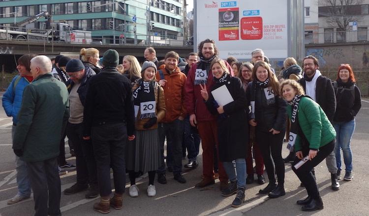 Circa 30 Leute stehen inmitten des tiefergelegten Parkplatzrondells unten am Österreichischen Platz und Grinsen um die Wette