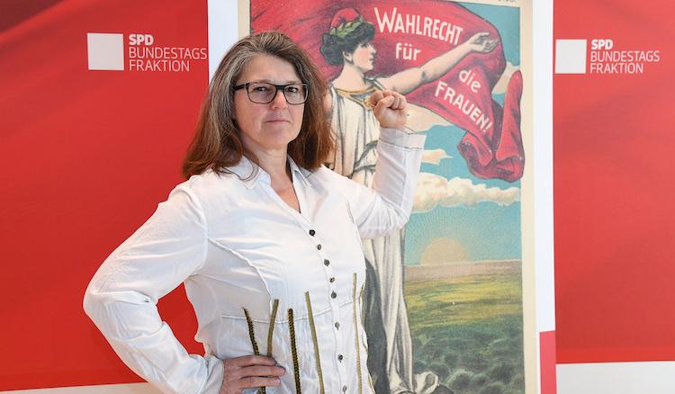 Ute Vogt vor einem historischen Plakat, auf dem damals das Wahlrecht für Frauen gefordert wurde