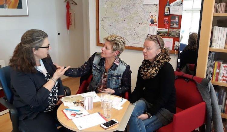 Ute Vogt sitzt mit den beiden Damen in ihrem Büro, dahinter eine bunt bestückte Pinwand und eine Karte Stuttgarts