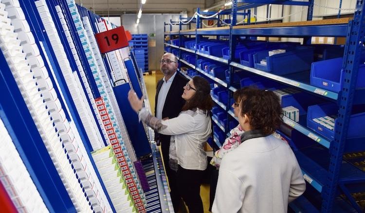 Ute Vogt und er Betriebsleiter stehen zwischen Hochregalen und Fließbandanlagen, auf die vollautomatisch Medikamentenpäckchen fallen.