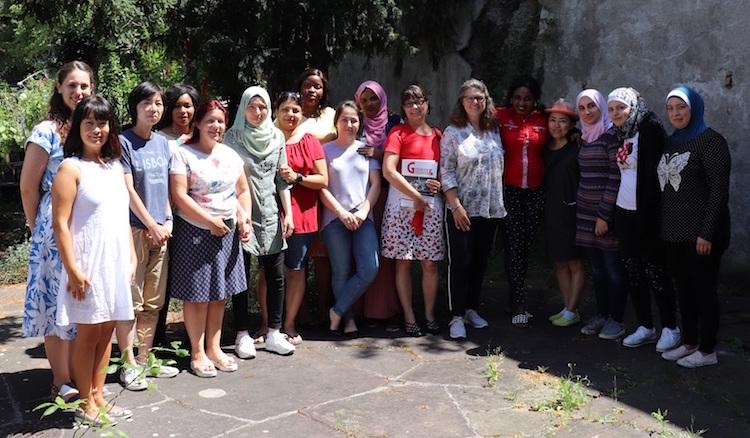 Die 15 Kursteilnehmerinnen gruppieren sich mit ihrer Sprachlehrerin und Ute Vogt im begrünten Hof.