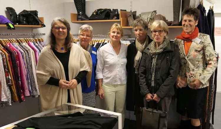 Ute Vogt steht mit den fünf Mitarbeiterinnen vor den Ständern mit Blusen und Jacketts, auf Regalen Schuhe und Handtaschen