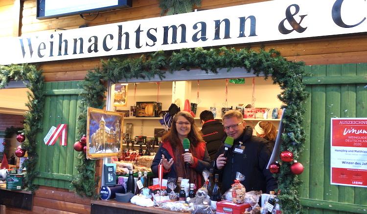 Am Verkaufsstand aus braunem Holz mit grünen Läden sind alle Geschenke aufgebaut, Ute Vogt und der Moderator stehen mit Mikrofonen dahinter.