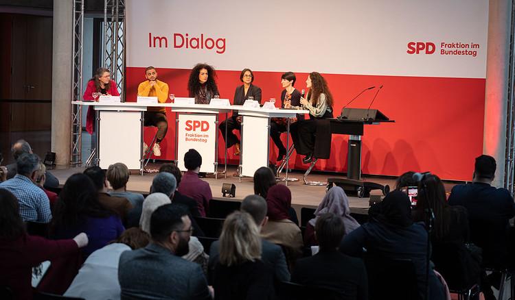 Vor einer weiß-roten Wand mit Logo der Fraktion sitzen die vier Podiumsteilnehmer, von hinten sieht man die ersten voll besetzten Stuhlreihen