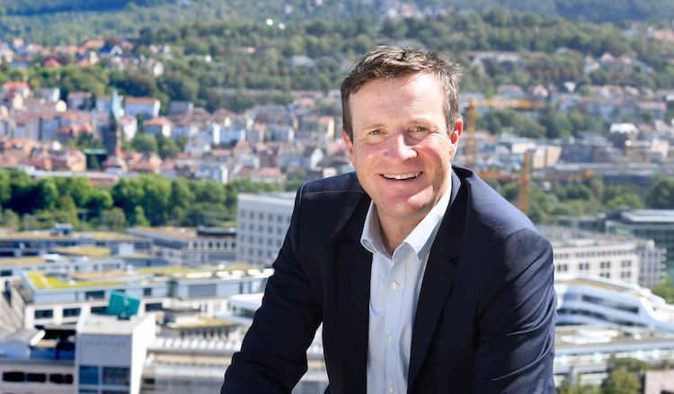 Martin Körner in Hemd und Sakko lächelt, im Hintergrund der Talkessel Stuttgarts