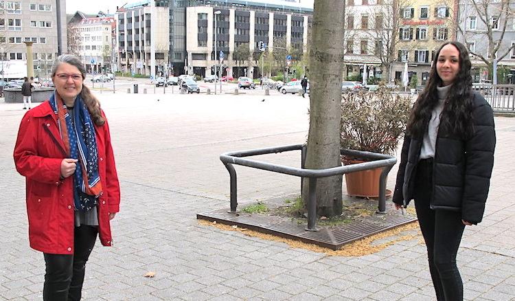 Ute in roter Jacke und Sanae in schwarzer stehen auf dem Wilhelmsplatz - im Hintergrund die Häuserzeilen