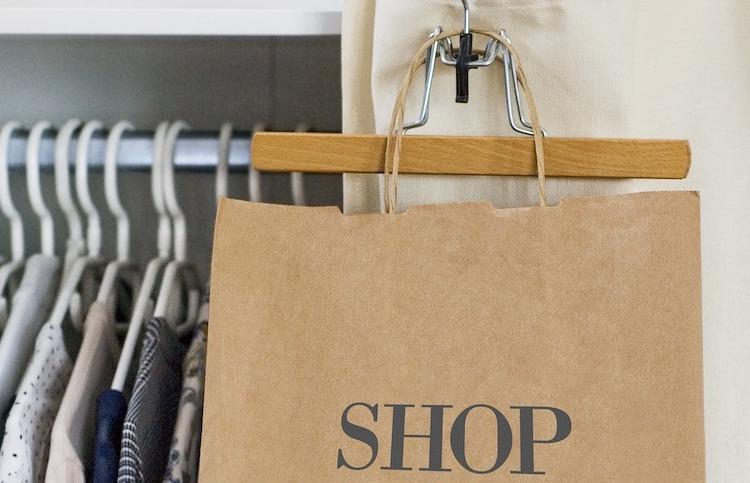 Kleider hängen im Schrank, außen an der Schranktür eine Papier-Einkaufstüte
